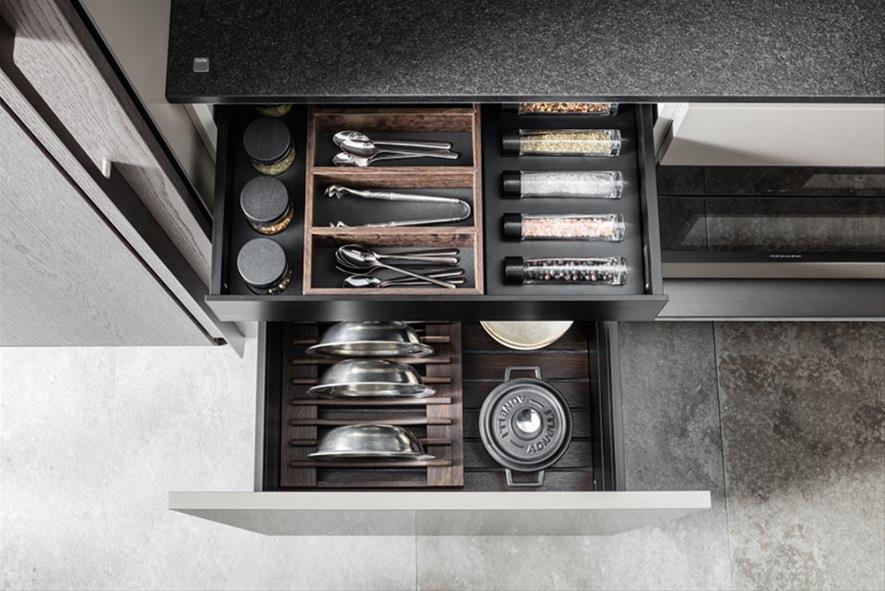 A drawer of accessories in steel arranged in different compartments.